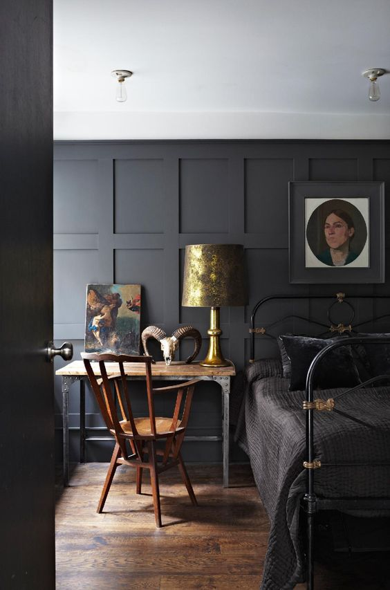 Charcoal feature wall combined with wood and brass creates a cozy, masculine room.