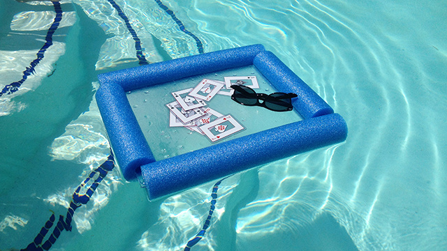 Use a styrofoam pool noodle and a cutting board to make a inflatable pool card table.